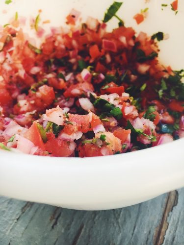 Pico de gallo on Vegetarian Fully Loaded Black Bean Nachos with Red and Green Salsas