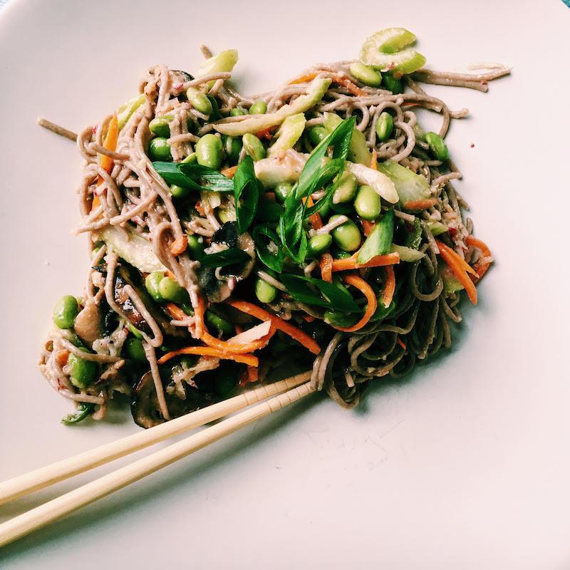 Soba salad with miso dressing, shredded carrots, mushrooms, edamame, radishes